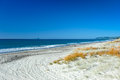 Wide expansive white sand beach ws a with rich azure blue sky south pacific ocean at pukehinau maketu bay of plenty new zealand Royalty Free Stock Photography