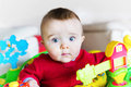 Wide eyed boy in jumper a baby a walker or pauses to look at the viewer Royalty Free Stock Photo
