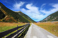 Wide fenced road in an alpine valley sunny autumn day the mountain slopes are covered with dense pine forest Stock Photography