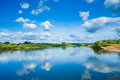 Wide river with reflection and green bush on coasts and blue clo of sky cloudy sky Royalty Free Stock Photos