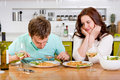 Wife enthusiastically looking while her husband eat pasta on the kitchen Royalty Free Stock Image