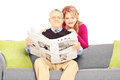 Wife hugging her husband seated on a sofa with newspaper isolated white background Stock Photo