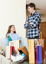 Wife showing purchases to disgruntled husband at home Stock Images