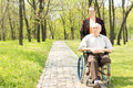 Wife walking a disabled man in a wheelchair men who has had one leg amputated through peaceful rural wooded park Royalty Free Stock Photography