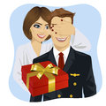 Wife in white bathrobe covering her husband s eyes wearing airline pilot uniform standing behind him with gift on blue background Royalty Free Stock Photos