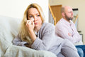 Wife wiping tears after family quarrel sad her with a handkerchief a conflict in a her stressed husband in sitting in a background Royalty Free Stock Images