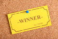 The wiining ticket winning golden raffle or lottery pinned to a cork notice board as a concept for being a winner or achiever Royalty Free Stock Images