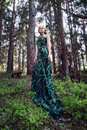 Wild beauty blonde woman long green dress in the forest spring sunny morning Royalty Free Stock Photography
