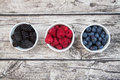Wild berries, Raspberries, blueberries and blackberries in bowls Royalty Free Stock Photo