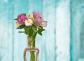 Wild flowers in vase on blue wood background Royalty Free Stock Photo