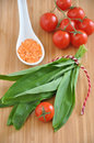 Wild garlic with tomatoes on a wooden board Royalty Free Stock Images