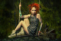 Wild girl tattooed redhead on a swing in a fantasy forest Stock Image