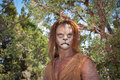 Wild lion man in forest a men stares cautiously at the camera with a background of this is the fantastic make up done by rayce Royalty Free Stock Image