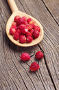 Wild strawberry in spoon on wooden background Stock Images