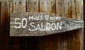 Wild west saloon sign rustic wooden pointing to next Royalty Free Stock Image