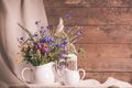Wildflowers in jug white ceramic and cups on tray Royalty Free Stock Image