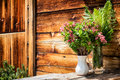Wildflowers at a log cabin Stock Photo