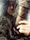 Wildlife Photographer in ghillie suit with camouflage DSLR camera with zoom telephoto lens
