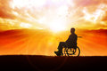 Will silhouette of a person on wheelchair in the outdoor with sunrise and mountain view as the background Stock Images