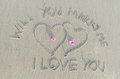 Will you marry me and heart drawn on sand sign of romantic and love Stock Image