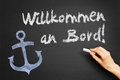Willkommen an bord welcome aboard hand writes in german on blackboard Royalty Free Stock Images