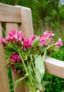 Wilting bunch of flowers seen left on a wooden bench in a cemetery. Royalty Free Stock Photo