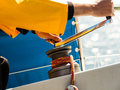 Winch capstan with rope on sailing boat male hand yachting yacht in blue baltic sea sunny day summer vacation tourism luxury Royalty Free Stock Photography
