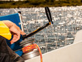 Winch capstan with rope on sailing boat male hand yachting yacht in blue baltic sea sunny day summer vacation tourism luxury Stock Image