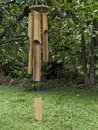 Wind chimes i a bamboo wood windchime on a leafy tree branch Stock Photos