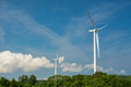 Wind energy for the future electricity generating windmills with a cloudy blue sky background standing above dense forest below Royalty Free Stock Photos