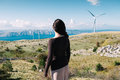 Wind energy woman looking turbines in the distance Royalty Free Stock Photography