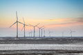 Wind farm in coastal mud flat power on the sunrise Royalty Free Stock Photography