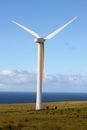 Wind generator in motion spins an open field overlooking pacific ocean Stock Image