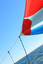 The wind has filled colorful spinnaker sail on sailing yacht detail of a against deep blue sky Royalty Free Stock Images