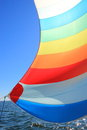 The wind has filled colorful spinnaker sail on sailing yacht detail of a against deep blue sky Royalty Free Stock Photo