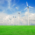 Wind mill power plant in green field  against blue sky Royalty Free Stock Photo