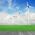 Wind mill power plant in green field and wood plant against blue sky Stock Images