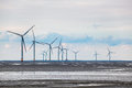 Wind power farm in coastal mud flat Royalty Free Stock Photo