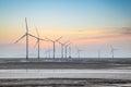 wind power farm on the coastal mudflat in sunrise Royalty Free Stock Photo