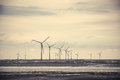 Wind power at the mud flat near sea shore turbine generating electricity Stock Photos