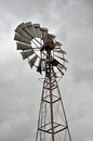 Wind pump for well water with a leaden dark cloudy sky Royalty Free Stock Images