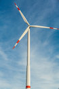 Wind turbine against a blue hazy sky in conceptual image of renewable and alternative energy resources to save the environment Royalty Free Stock Photo