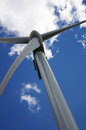 Wind turbine against a blue sky with cloud Royalty Free Stock Image