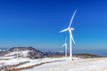 Wind turbine and blue sky in winter. Royalty Free Stock Photo