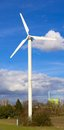 Wind turbine and factory in front of a cloudy spring sky Royalty Free Stock Image