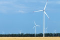 Wind turbine farm above land used for agriculture stretching Royalty Free Stock Image