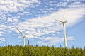 Wind turbine generating electricity windmills on forest and sky with clouds Stock Images