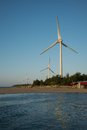 Wind turbine white generating electricity on sea Stock Images