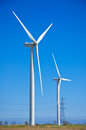 Wind turbines on bright sunny day next to electricity pylons Royalty Free Stock Photos