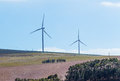 Wind turbines with clouds in the background and trees in the foreground an image showing generating electricity middle ground Stock Photos